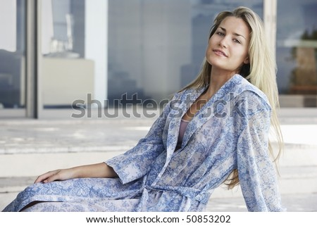 Young woman wearing bathrobe sitting outdoors, portrait