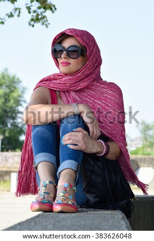 young woman wearing big sun glasses and pink scarf around her head  relaxing outside