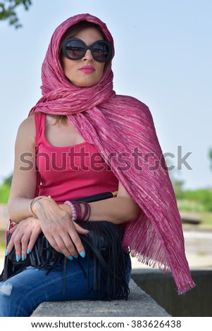 young woman wearing big sun glasses and pink scarf around her head  relaxing outside  - stock photo