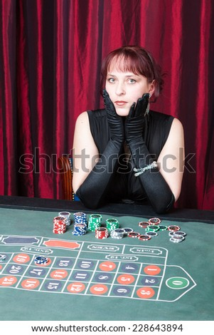 young woman wearing black dress and gloves playing in casino - stock photo