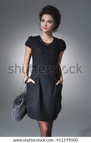 Young woman wearing black dress with bag on light background