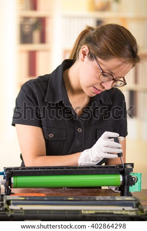 Young woman wearing black shirt performing toner change and printer maintenance, concentrated facial expressions. - stock photo
