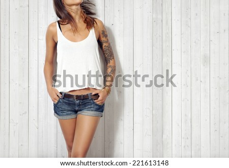 Young woman wearing blank vest. Wood wall background. - stock photo