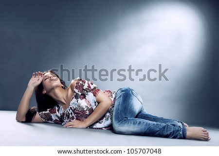 young woman wearing blue jeans lying on the floor in blue spotlight - stock photo