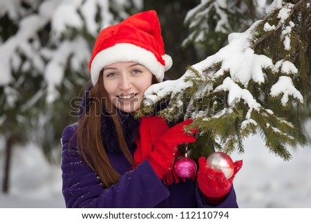 Young woman  wearing christmas hat decorates  spruce outdoors - stock photo