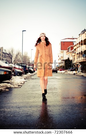 young woman wearing coat walking down the street, cold winter day