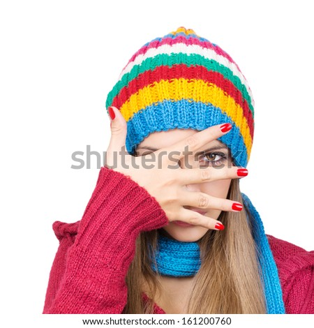 Young woman wearing colorful hat hiding behind her hand - stock photo