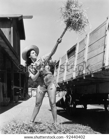 Young woman wearing cut off jeans and working at the farm pitching hay into a wagon - stock photo
