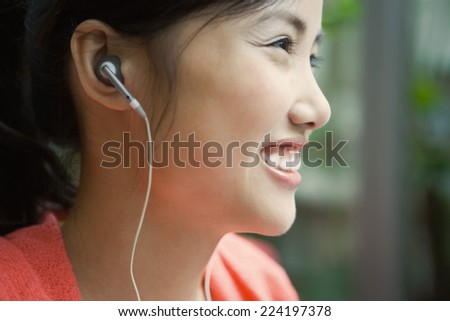 Young woman wearing earphones, smiling, close-up, profile - stock photo