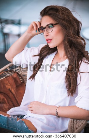 young woman wearing eyeglasses sit and relax in cafe outdoor natural light