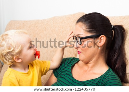 Young woman wearing eyeglasses with child boy playing on sofa. - stock photo