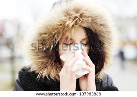 Young woman wearing furry hood, sneezes during cold day. Woman is holding tissue next to her nose. - stock photo
