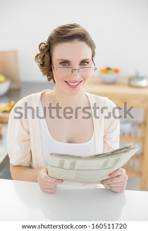 Young woman wearing glasses for reading newspaper in her kitchen looking at camera - stock photo
