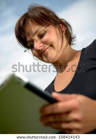 Young woman  wearing glasses works with tablet computer