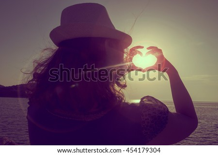 Young woman wearing hat, standing on the beach in Syvota bay, Greece, looking at sunset and making a heart shape with her hands, circling the Sun - stock photo