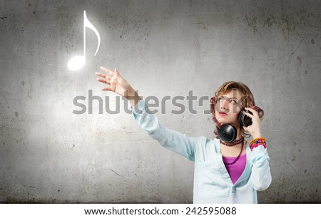 Young woman wearing headphones and enjoying music - stock photo