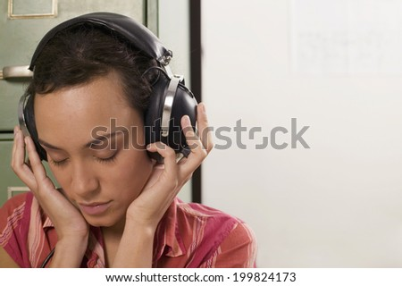 Young woman wearing headphones with eyes closed