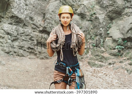 Young woman wearing in safety harness with climber equipment and helmet holding rope and looking at camera on background of rock - stock photo