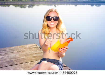 Young woman wearing in yellow swimsuit with sun shape with thumbs up gesture on the shoulder on the beach