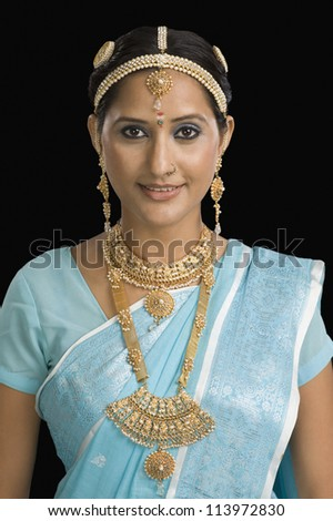 Young woman wearing jewelry and smiling - stock photo
