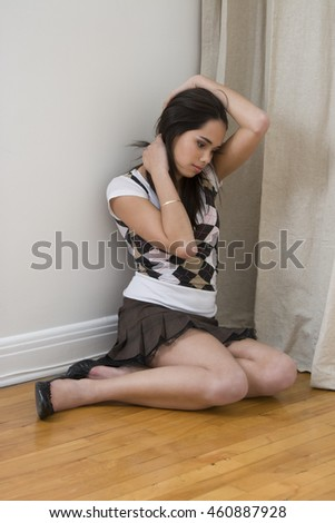young woman wearing mini skirt and shirt sitting on the floor, holding her hair, with sad expression