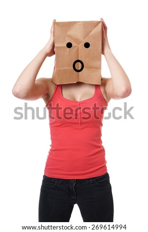 young woman wearing paper bag with shocked smiley face over her head - stock photo