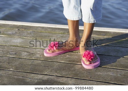Young woman wearing pink daisy flip-flops - stock photo