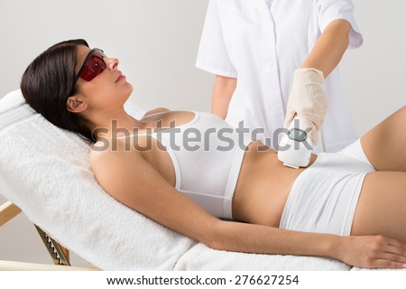 Young Woman Wearing Protective Glasses Receiving Laser Treatment On Belly At Beauty Clinic - stock photo