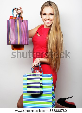 young woman wearing red dress with shopping bags.