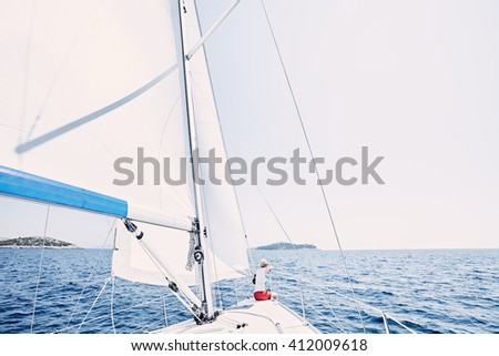 Young woman wearing red shorts, sitting on deck under sails on yacht bow and enjoying wonderful view to islands in peaceful sea during summer sailing holidays - yacht charter concept - stock photo