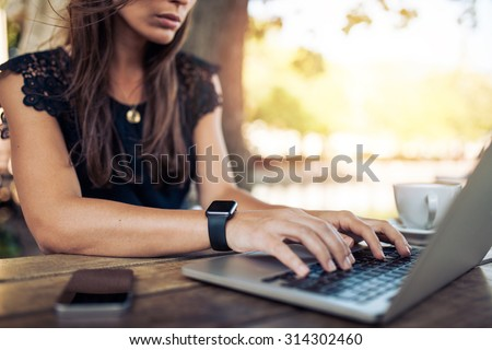 Young woman wearing smartwatch using laptop computer. Female working on laptop in an outdoor cafe. - stock photo