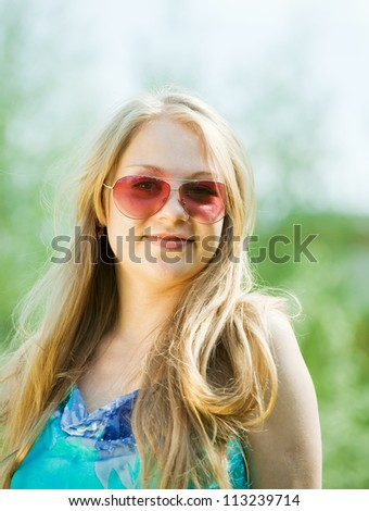 young woman wearing sunglasses against nature - stock photo