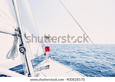 Young woman wearing sunglasses and red shorts, standing on deck under sails on yacht bow, enjoying wonderful view to peaceful sea looking far covering her eyes by hand during summer sailing holidays