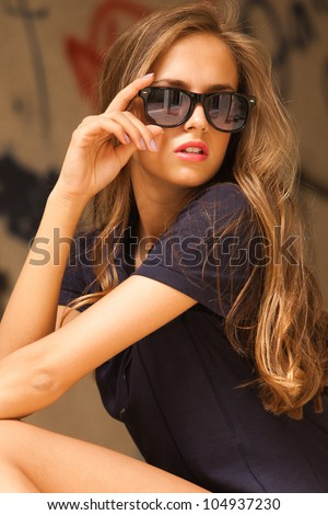 young woman  wearing sunglasses sit on stairs in front of graffiti city wall - stock photo