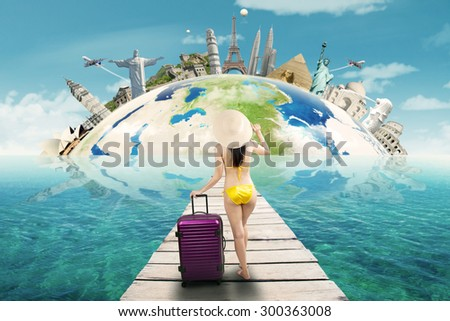 Young woman wearing swimwear standing on the jetty while carrying bag to holiday on the worldwide monuments - stock photo