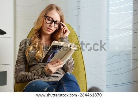 Young woman wearing warm sweater relaxing on cozy chair and reading book at home - stock photo