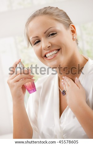 Young woman wearing white silk bathrobe applying perfume, smiling. - stock photo