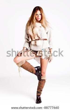 young woman wearing winter clothes, full body shot, studio shot - stock photo