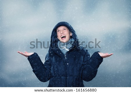 young woman wearing winter clothes  is excited about the snowfall - stock photo