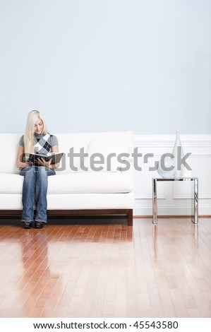 Young woman wears a checkered top and blue jeans while sitting on white sofa.  She is reading a book. Vertical shot. - stock photo