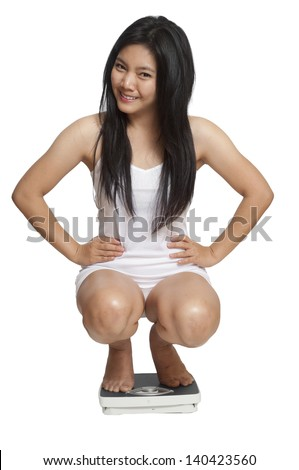 Young woman weighing herself on a scale and is happy with the results - stock photo