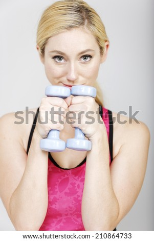 Young woman weight training with dumb bells