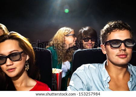 Young woman whispering in boyfriend's ear while watching movie in cinema theater - stock photo