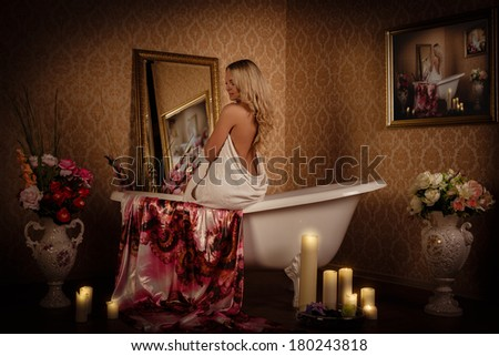Young woman wiping body by a towel in house  bathroom. Concept  of body care.