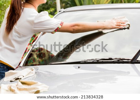 young woman,wiping car with microfiber cloth after washing. - stock photo