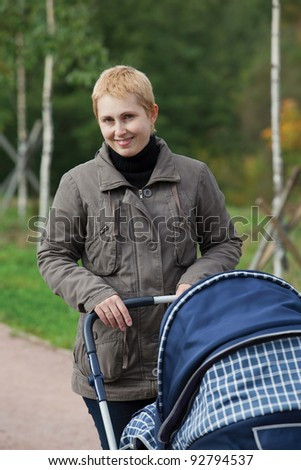 young woman with a baby in the pram walking in the park