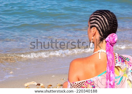 Young woman with a beautiful Afro hair sitting on the shore and looks at sea, Beauty sea, summer and youth, Photography - stock photo