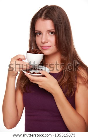 young woman with a beautiful smile holding a white coffee cup full of coffee beans on a white background on Food and Drink