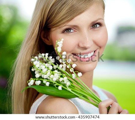 Young woman with a beautiful smile with healthy teeth with flowers. Face of a beautiful positive girl  Concept on the subject of dentistry, stomatology, dental care. - stock photo