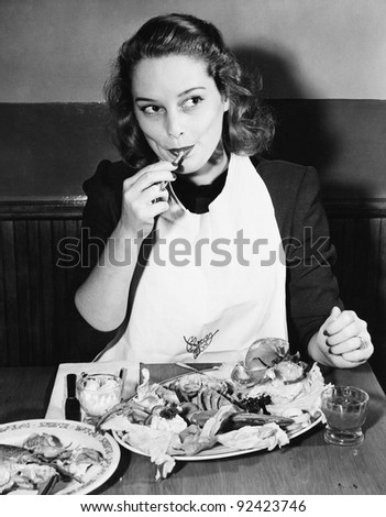 Young woman with a bib eating Lobster - stock photo